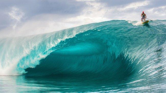 Серфер с веслом на гребне волны
