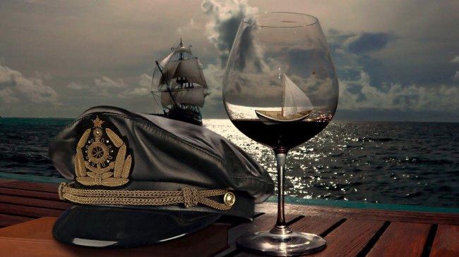 На столе бокал с красным вином и фуражка