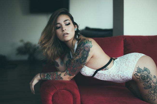 Девушка с татуировкой на теле позирует на диване