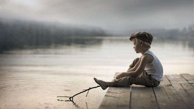 Мальчик сидящий на мостике, водит прутиком по воде