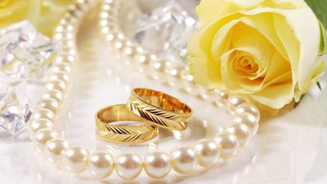Два обручальных кольца возле желтой розы и нити жемчуга