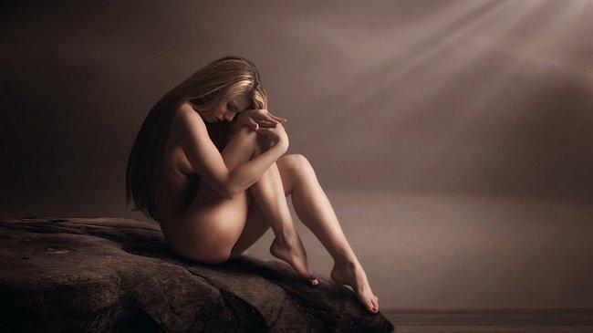Обнаженная девушка сидя склонила голову на колени
