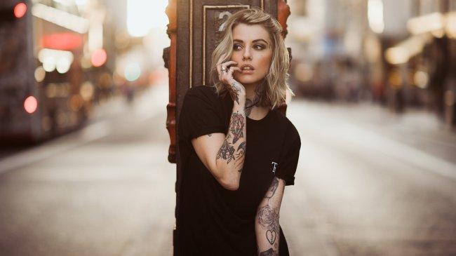 Красивая девушка с татуировками на руках