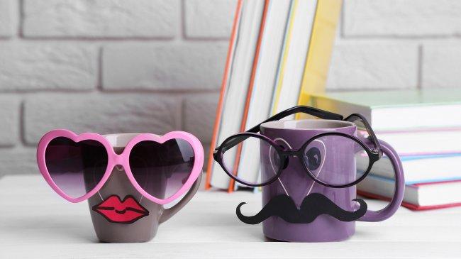 Две кружки в очках стоят возле книг