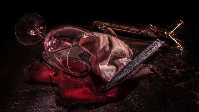Кинжал рядом с пролитым красным вином