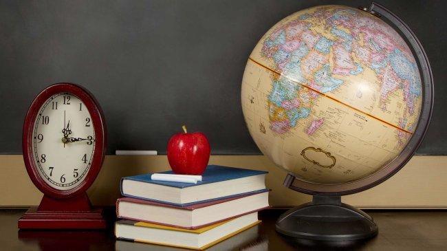 Глобус учебники и часы стоят на учительском столе.