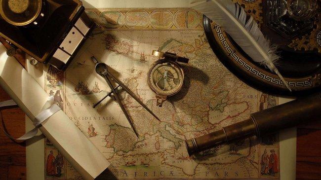 Подзорная труба, компас, циркуль, перо лечат на карте