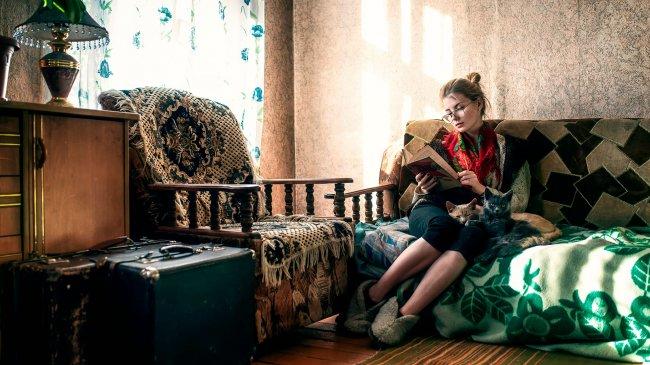 Девушка на диване с книгой