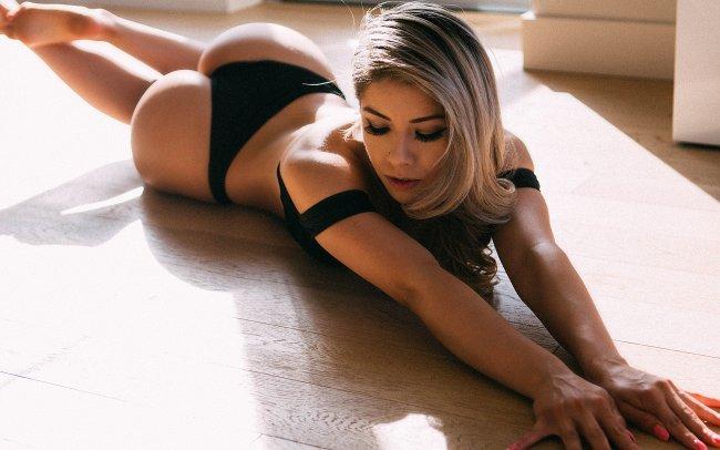 Блондинка в черном нижнем белье лежит на полу