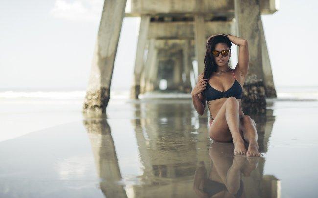 Девушка сидит на берегу моря под мостом