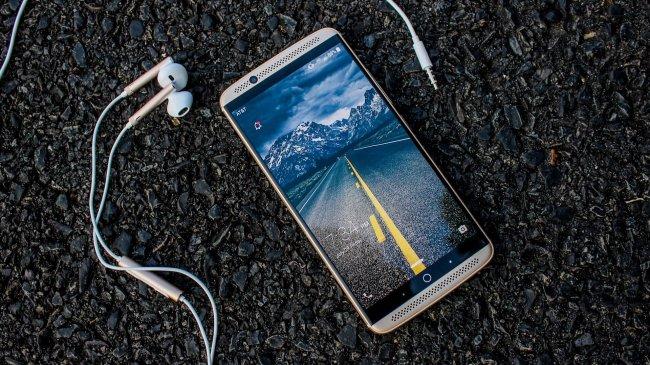 Смартфон с наушниками лежит на асфальте