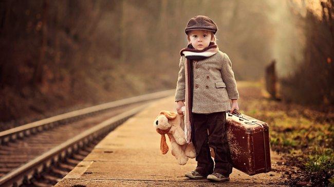 Мальчик с чемоданом стоит на перроне