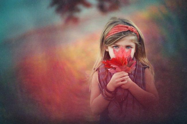 Девочка с осенними кленовыми листьями