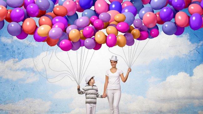 Женщина и мальчик держат много воздушных шаров