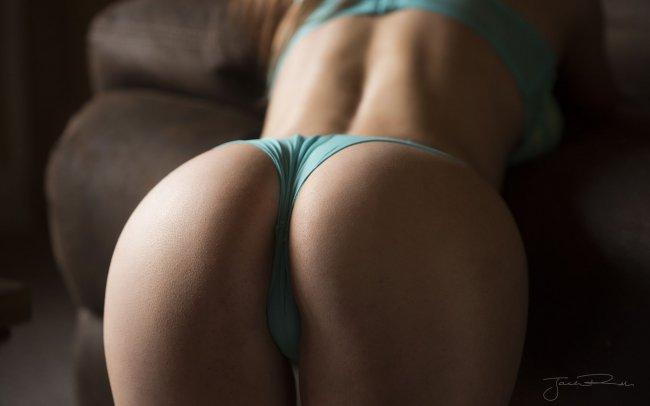 Девушка в нижнем белье позирует у дивана