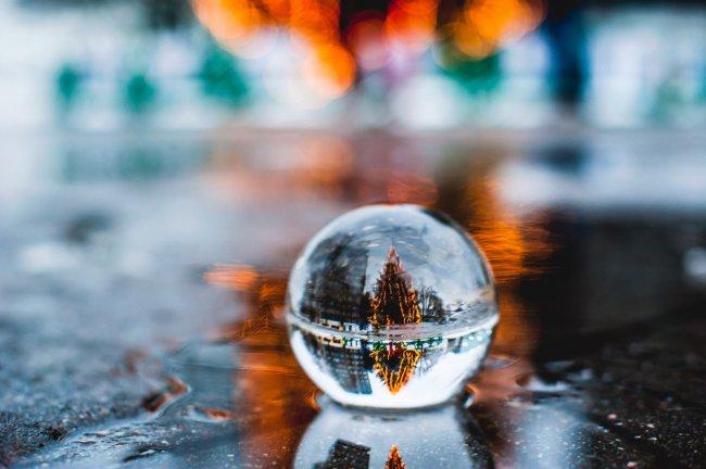 В стеклянном шаре отражается городская улица с новогодней елкой