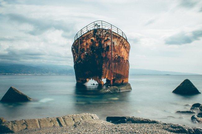 Старый ржавый корабль у берега моря