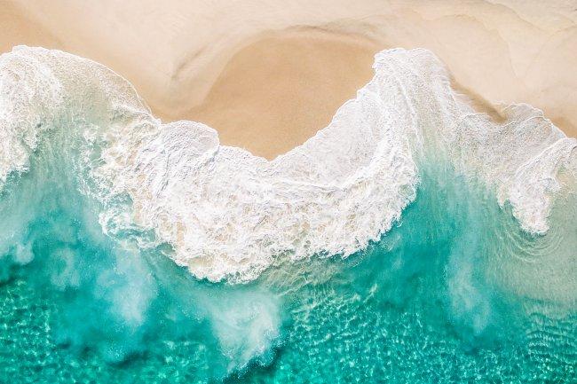 Морские волны омывают песчаный берег