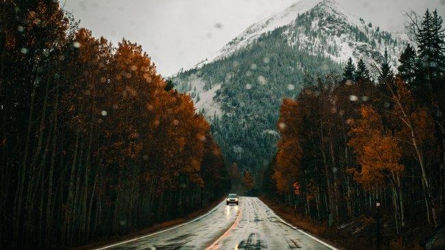 Автомобиль на мокрой дороге среди деревьев на фоне заснеженной горы