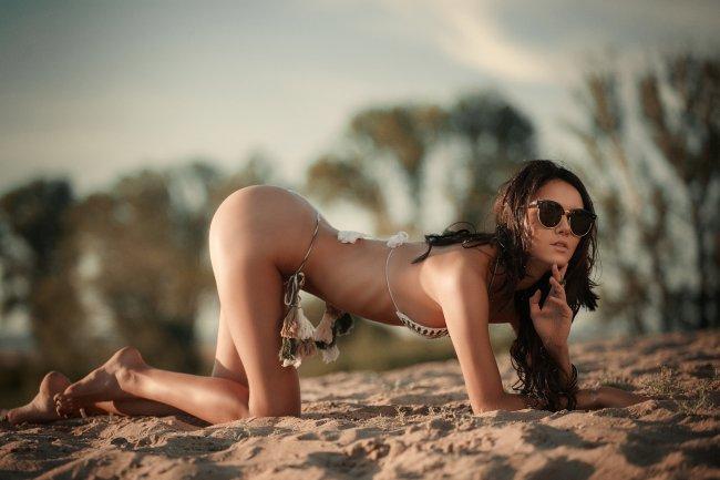 Красивая брюнетка в очках позирует на пляже в бикини