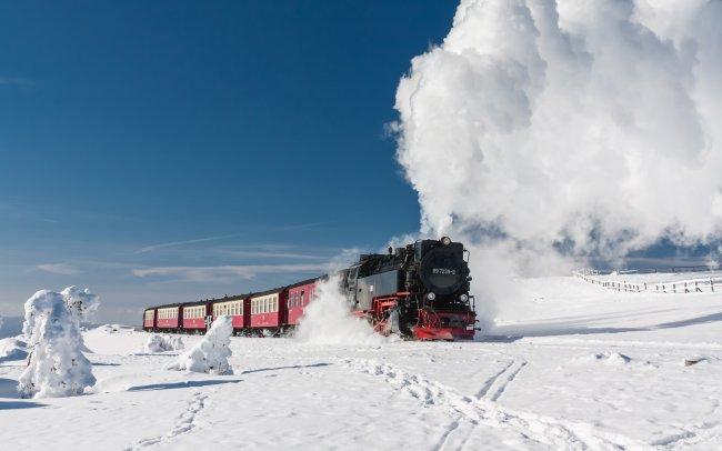 Мчащийся локомотив по заснеженным рельсам