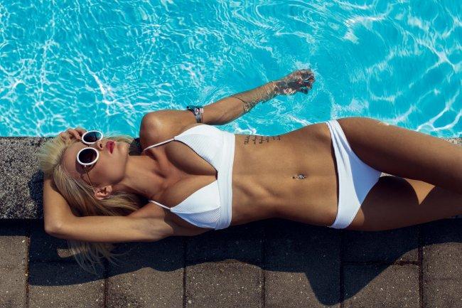 Блондинка в белом бикини у бассейна