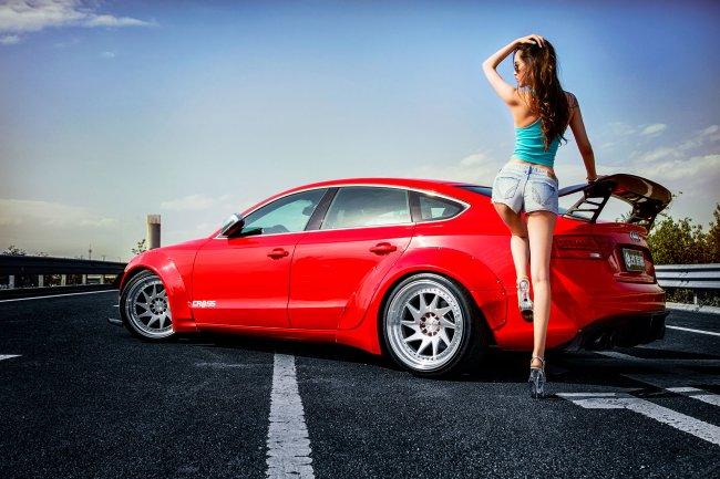 Девушка стоит у автомобиля Audi A5 Cross