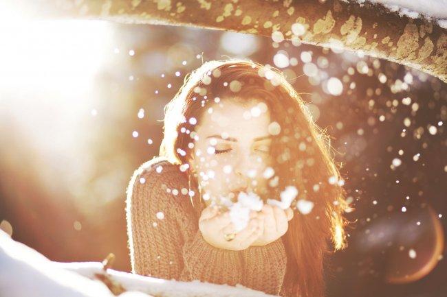 Девушка сдувает снег с ладоней