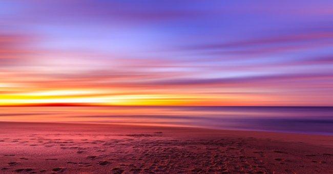 Песочный пляж на фоне яркого красочного заката