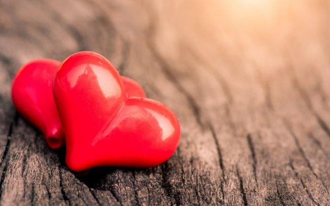 Два красных сердца на деревянном фоне