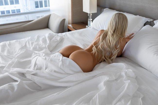 Красивая голая блондинка в белоснежной постели
