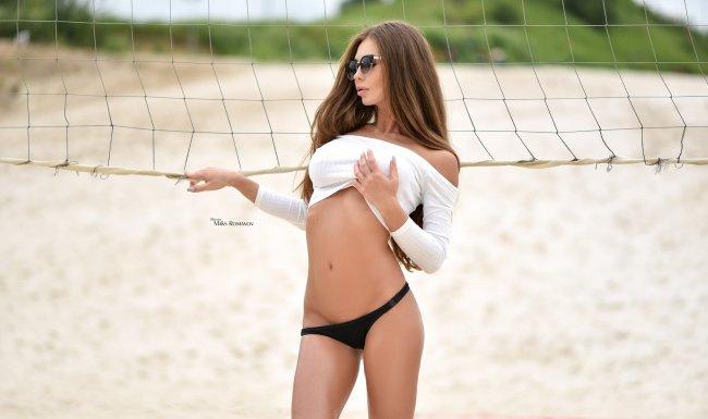 Девушка в солнечных очках позирует на теннисной площадке