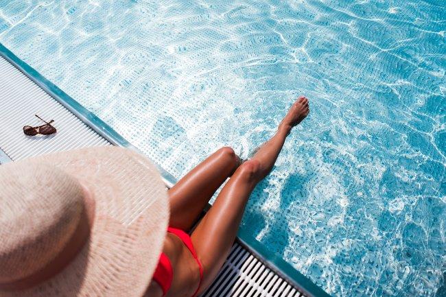 Девушка в бикини отдыхает у роскошного бассейна