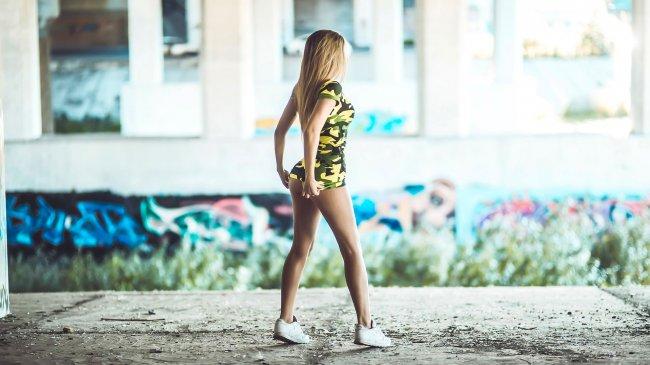 Девушка в камуфляжной футболке и кроссовках