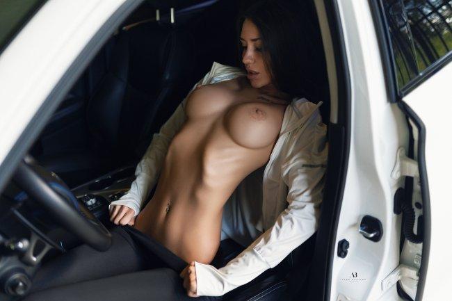 Брюнетка с обнаженной грудью в салоне автомобиля
