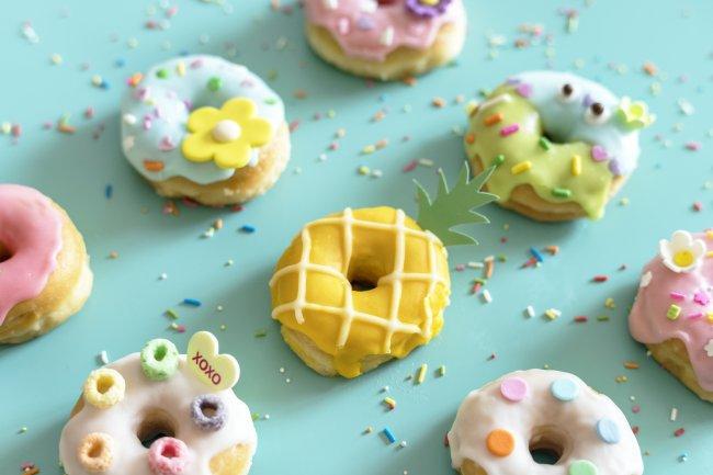 Вид сверху на пончики в цветной глазури и сахарной посыпке