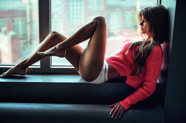 Девушка с красивыми ногами на подоконнике