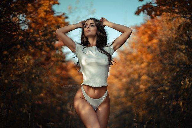 Стройная девушка на фоне осенних деревьев