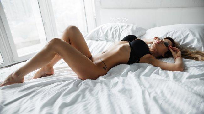 Сексуальная девушка в очках лежит на кровати
