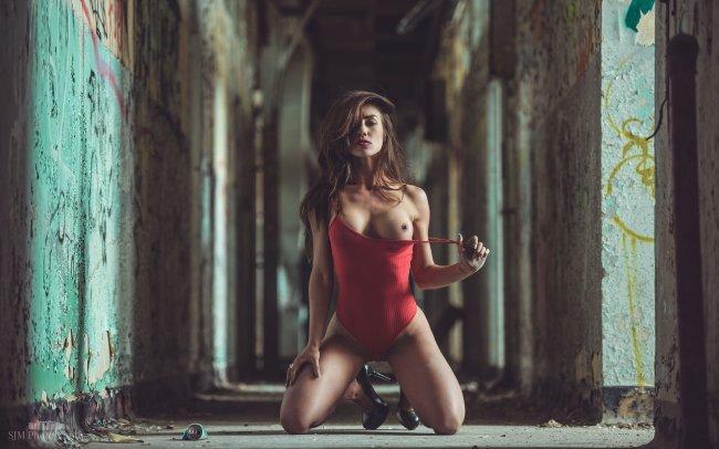Девушка в красном боди позирует стоя на коленях