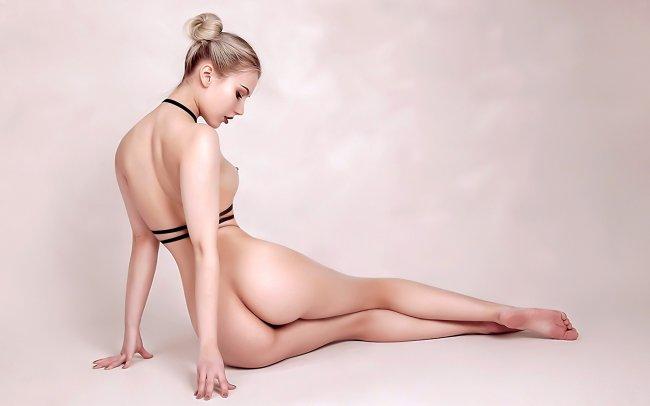 Обнаженная блондинка сидя на полу