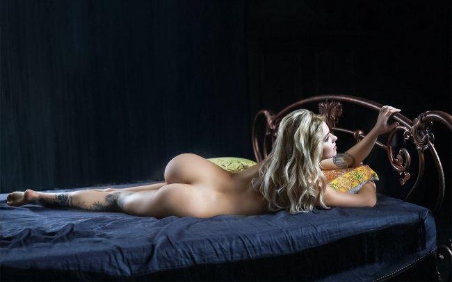 Блондинка позирует голая в постели