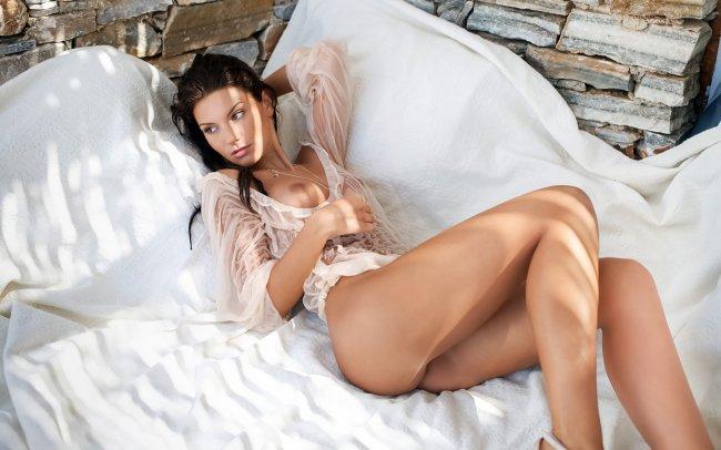 Красивая брюнетка позирует в постели