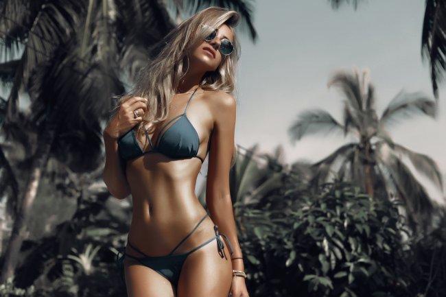 Загорелая девушка в купальнике на фоне пальм