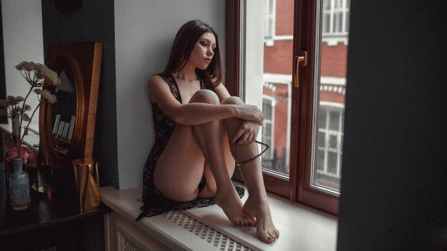 Девушка сидит на подоконнике у окна