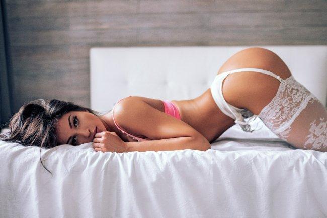 Красивая девушка в нижнем белье позирует на кровати