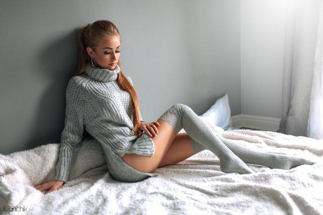 Девушка в вязаном свитере на кровати