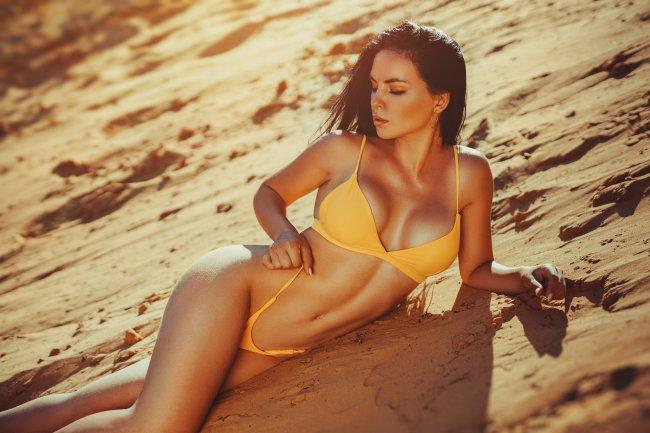 Молодая сексуальная брюнетка в нижнем белье на песка
